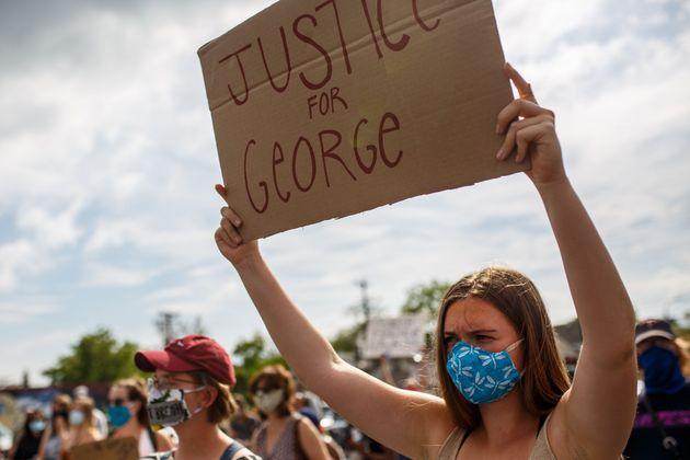 5月26日に開かれた抗議活動で、「ジョージに正義を」と抱えたカードを掲げる参加者