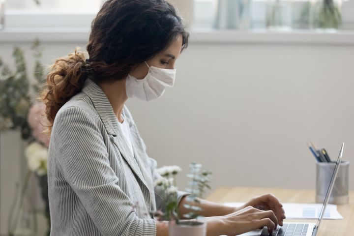 Side view of young businesswoman wearing face mask protects herself from getting flu or coronavirus COVID19 pandemic infectious disease, working typing on computer seated at workplace in office room