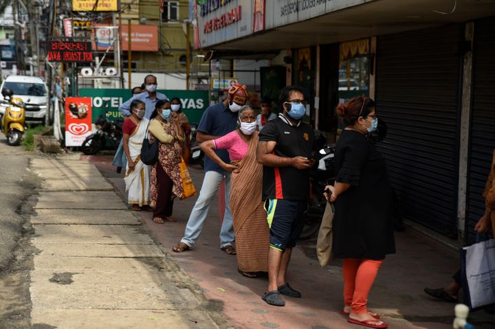 People wearing masks as a precaution against the coronavirus line up outside a government ration shop in Kochi, Kerala, May 20, 2020.