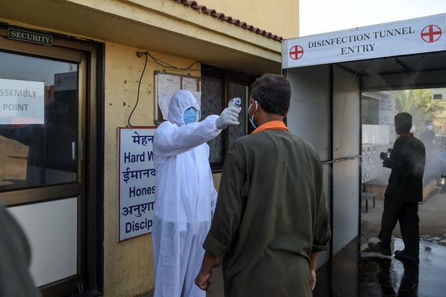 A health worker checks the body temperature of a worker at DH Cube Industries at Vasna Buzarg village,...