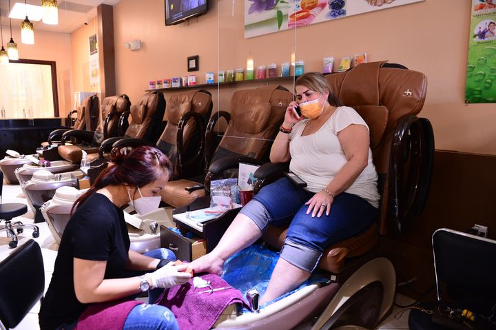 Nail technician Jimmie and her customer wear masks during a pedicure at Nails and Spa salon on May 20, 2020, in Miramar, Florida.