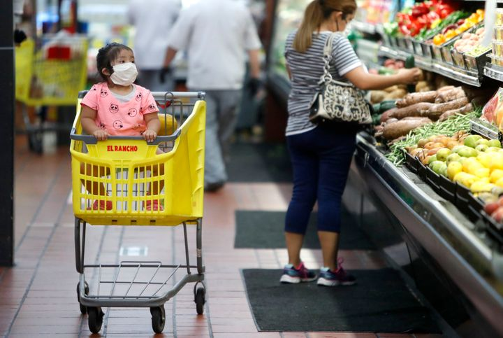 Amid concerns of the spread of COVID-19, a little girl wears a mask at El Rancho grocery store in Dallas on May 12, 2020.