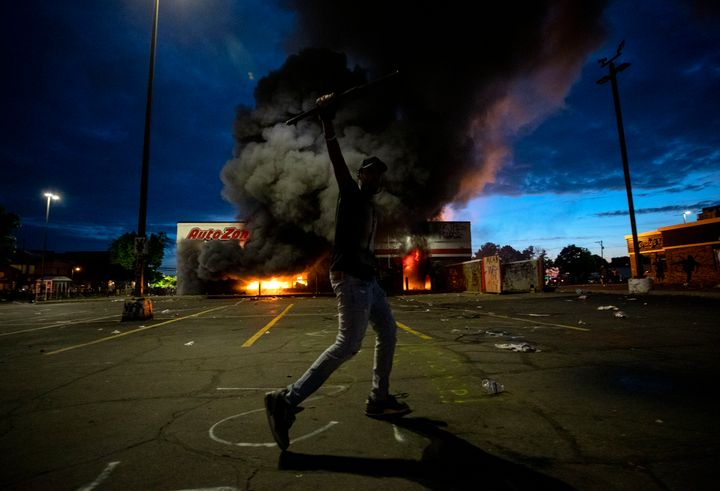 A man poses for a photo in the parking lot of an AutoZone store in flames, while protesters hold a rally for George Floyd in