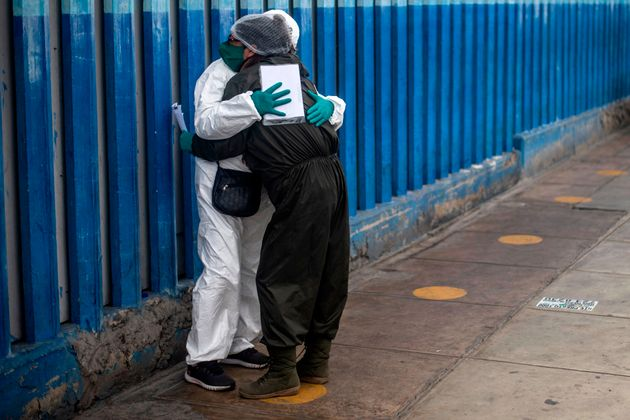 A woman mourns the dead of her husband victim of the new coronavirus, COVID-19, outside the emergency area at Alberto Sabogal Hospital in Lima, on May 27, 2020. - Peruvian Health Minister insisted on Wednesday, that Peru has entered a plateau in the curve that registers the expansion of new coronavirus infections, a day after the Pan American Health Organisation (PAHO) warned that COVID-19 transmission is accelerating in this country as in Brazil and Chile. (Photo by ERNESTO BENAVIDES / AFP) (Photo by ERNESTO BENAVIDES/AFP via Getty Images)