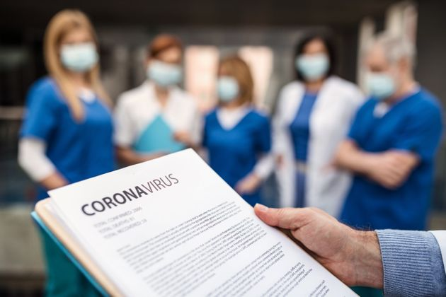 A group of doctors with face masks talking about corona virus on