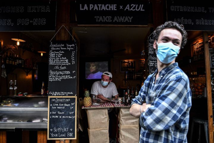 A bartender selling take-away drinks and food waits for customers behind a makeshift counter along the sidewalk in Paris on M