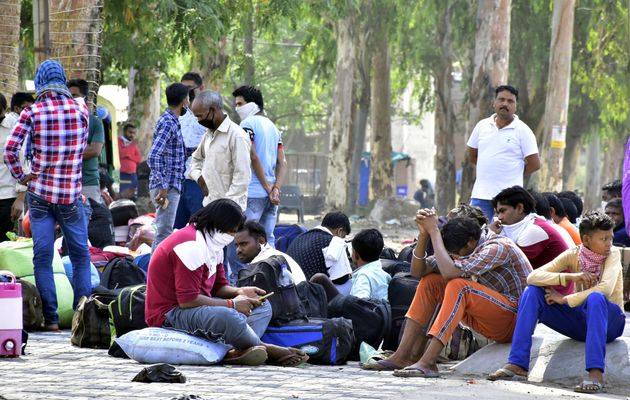 Migrants wait to be thermal screened at Majitha road bypass before being ferried to the railway station...
