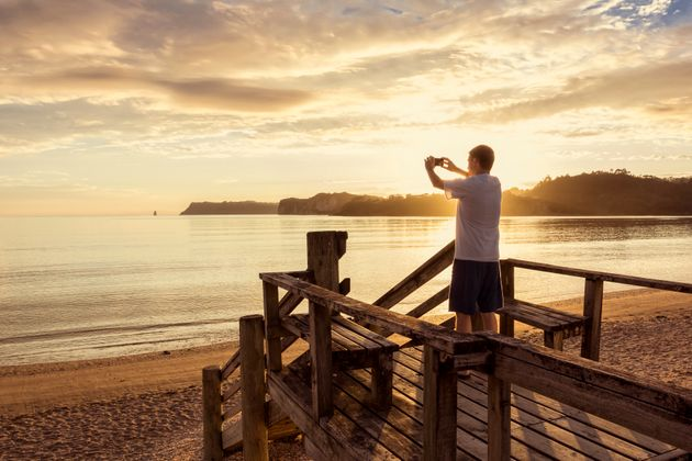 A man taking a photo with his phone as he enjoys a peaceful morning