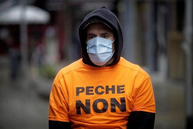 Un trabajador de Alcoa, con mascarilla, viste una camisera contra el