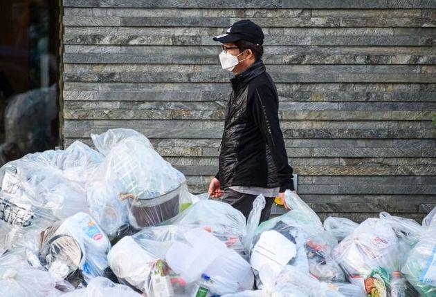 Una persona camina con mascarilla junto a una montaña de residuos de plástico en Nueva
