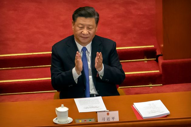 Chinese President Xi Jinping applauds during the closing session of China's National People's Congress...