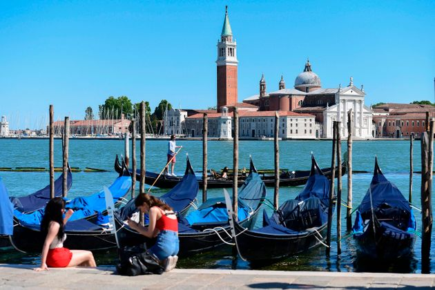 Young women sit at an embankment by gondolas moored opposite the San Giorgio Maggiore church (Rear) in...