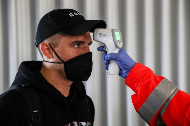 Un trabajador mide la temperatura a un ciudadano antes de un partido de fútbol en