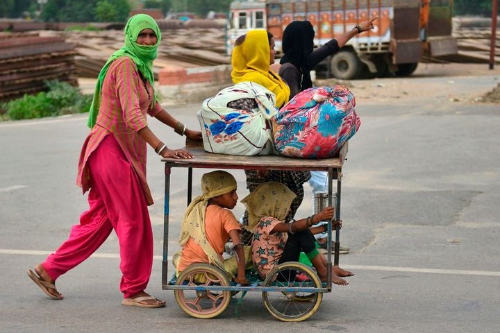 Migrants labourers walk on a road as they wait for transportation to go back to their hometowns in Allahabad on May 24, 2020.