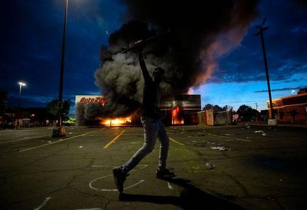 炎に包まれるオートゾーンの駐車場で、カメラに向かってポーズをとる人物。