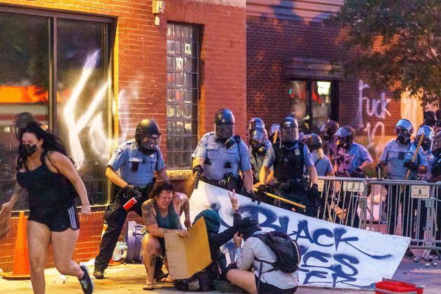 抗議活動の参加者たちに、ペッパースプレーを浴びせる警察