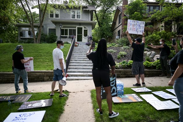 Protesters angered by the death of George Floyd stand Wednesday outside the home of Hennepin County Attorney...