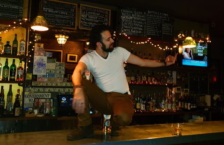 Kenneth John Jimenez, 36, working at a bar in Brooklyn, New York, where he made $9 an hour plus tips. Now he's getting $600 a