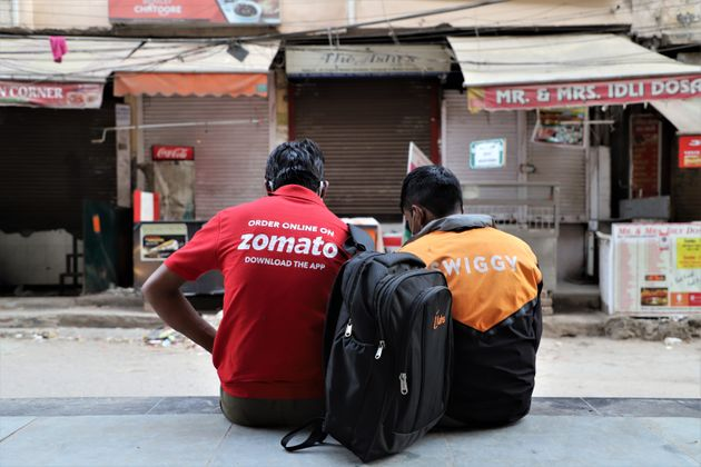 Swiggy and Zomato delivery partners rest near closed restaurants in DLF Phase III, Gurugram on the outskirts...