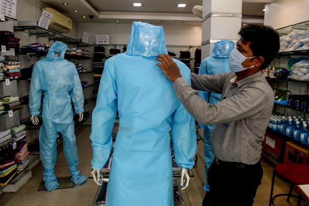 A shopkeeper arranges a protective suit for sale on a mannequin at a garment shop after the government...