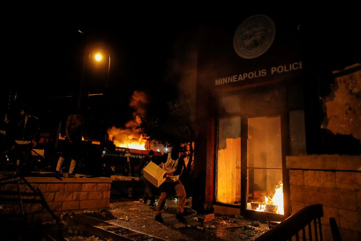 A protester sets fire to the entrance of a police station in Minneapolis. REUTERS/Carlos Barria