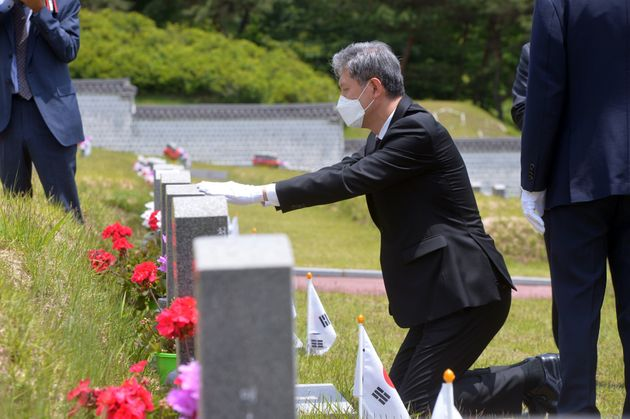 노태우 전 대통령 아들 노재헌씨가 29일 광주 북구 운정동 국립5·18민주묘지에서 헌화·분향을 한 뒤 묘역 앞에 무릎 꿇고 묘비를 어루만지고