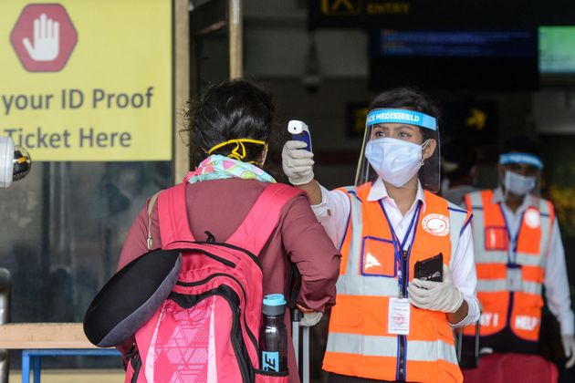 An airport employee wearing a face shield checks the body temperature of a passenger at Bagdogra airport...