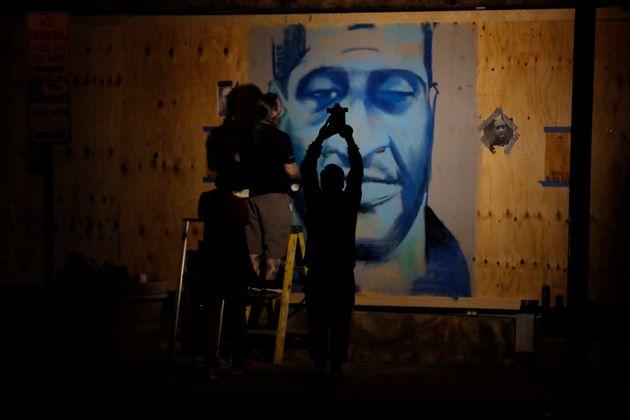 An artist creates an image of George Floyd in Minneapolis. (AP Photo/Julio