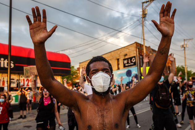 A protester wearing a face mask holds up his hands during a May 27 demonstration outside Minneapolis'...