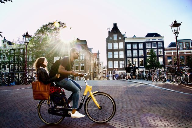 A man rides a bicycle with a woman on the back in Amsterdam. Bikes are part of daily life in the