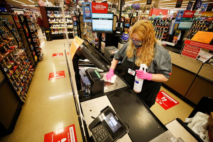 A worker at a Vons grocery store in Torrance, California, sanitizes her work station.