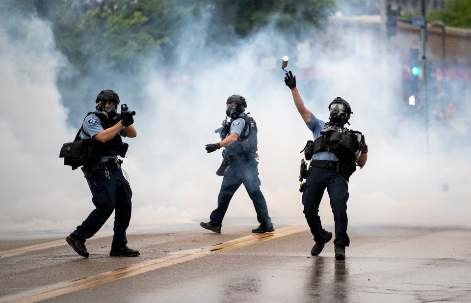 A police officer throws a tear gas canister towards protesters at the Minneapolis 3rd Police Precinct,...