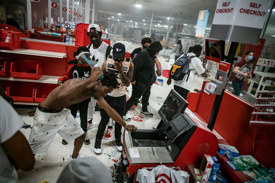 A looter uses a claw hammer as he tries to break in to a cash register at a Target store in