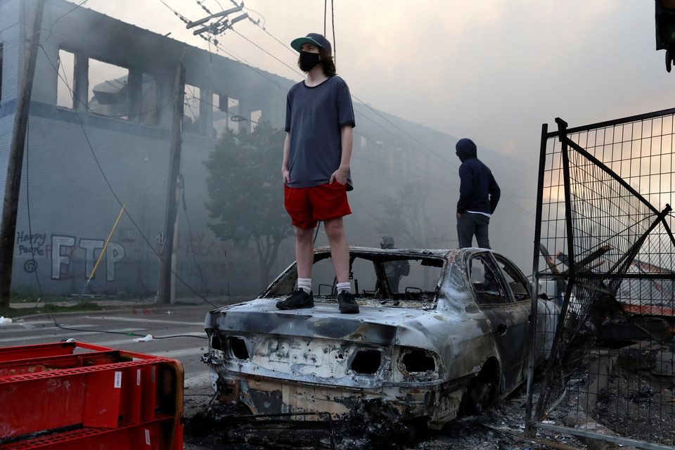 People stand on a burned up car as fires burn near a Target Store early