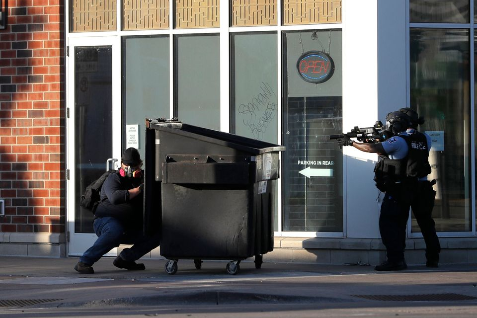 A protester hides behind a dumpster he pulled as a barrier while St. Paul Police officers move in to...