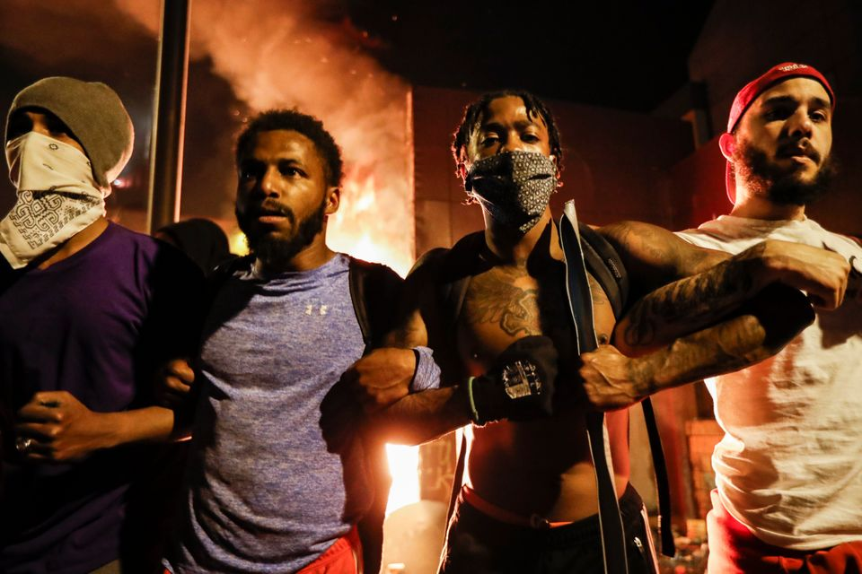 Protestors demonstrate outside of a burning Minneapolis 3rd Police Precinct,