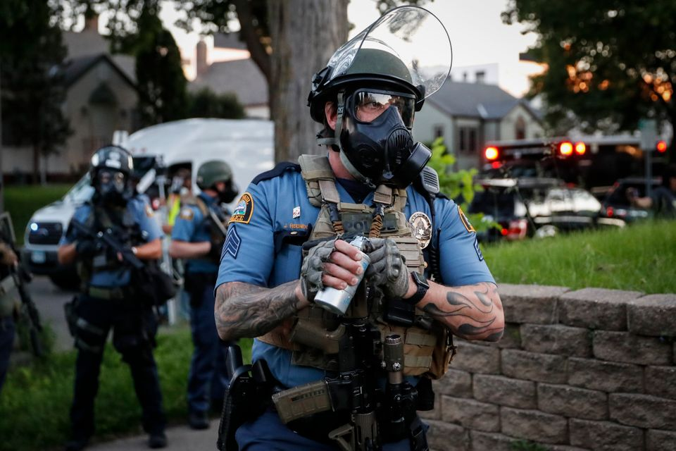 A police officer prepares to throw a tear gas canister towards protestors on