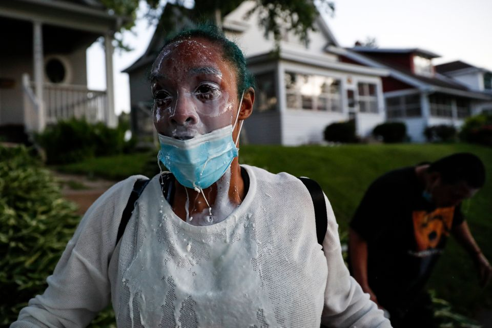 A protestor douses her face with milk after being exposed to tear gas fired by