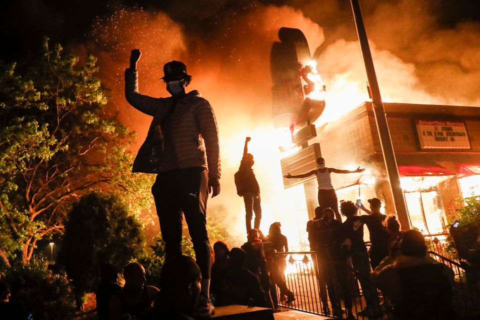 Protestors demonstrate outside of a burning fast food