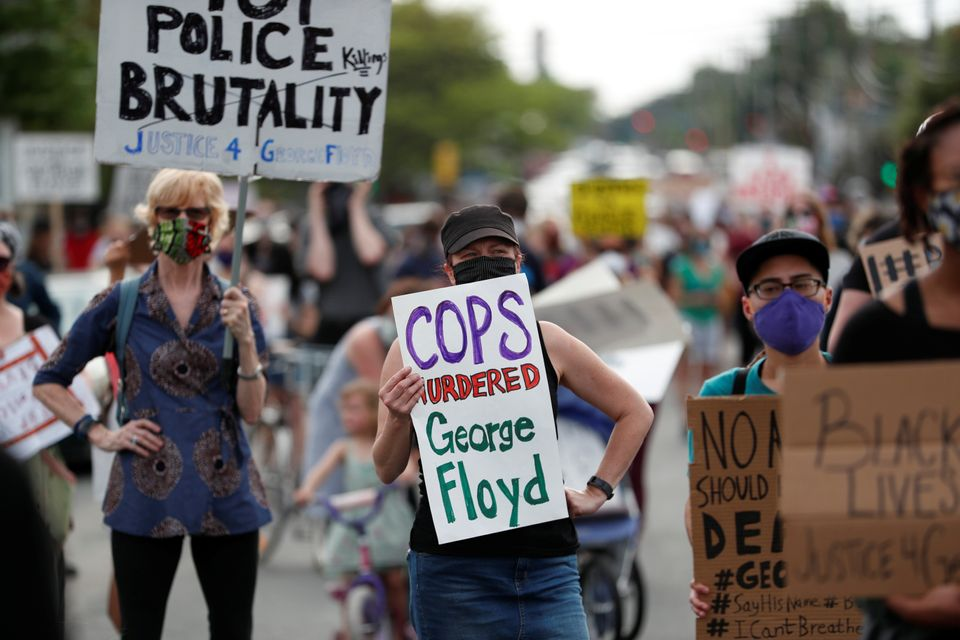 Protesters gather at the scene where George Floyd was pinned down by a police officer kneeling on his...