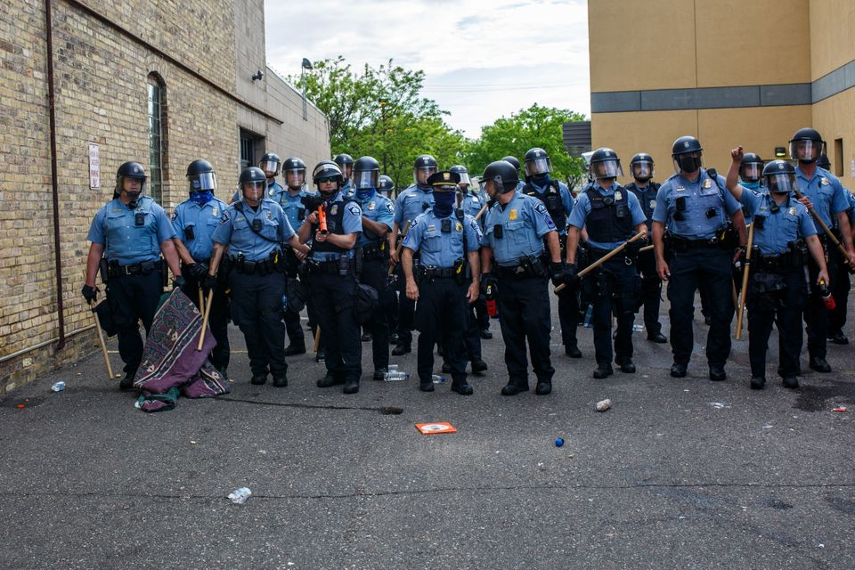 Police officers stand in a line while facing protesters demonstrating against the death of George Floyd...