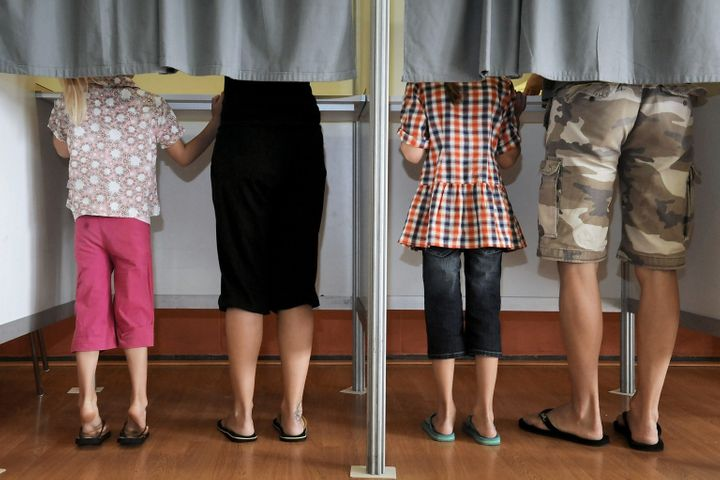 Parents in Brakel, Belgium, vote with their kids during Federal Election Day on June 13, 2010. Belgium, where voting is manda