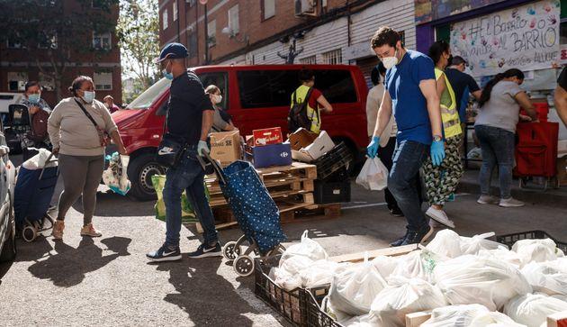 Una cola de ciudadanos del barrio de Aluche hacen colan para recoger