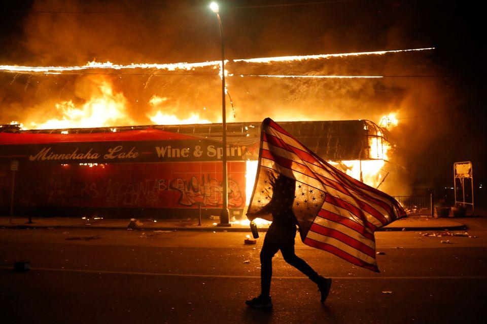 Um manifestante carrega um bandeira dos EUA de cabeça para baixo ao lado de um prédio em chamas na quinta (28), em Minneapolis.
