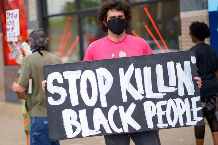 "A man holds a ""Stop Killing Black People"" sign on May 26, 2020, near the area where Minneapolis police killed George Floyd."