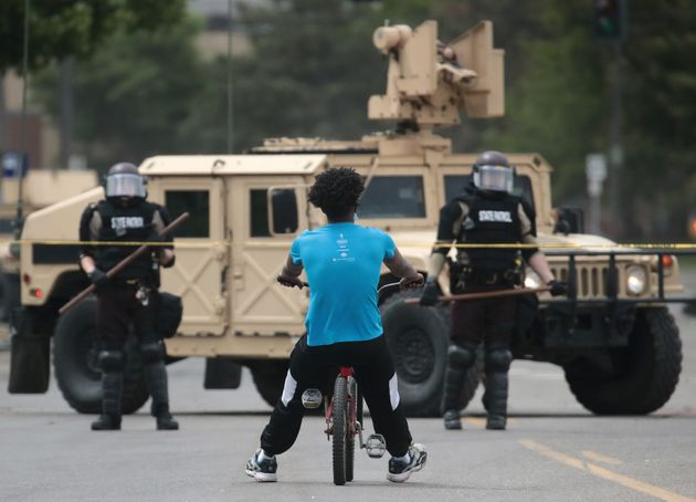 A man rides a bicycle up to a law enforcement checkpoint Friday in