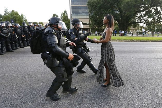 Lone activist Ieshia Evans stands her ground while offering her hands for arrest as she is charged by...