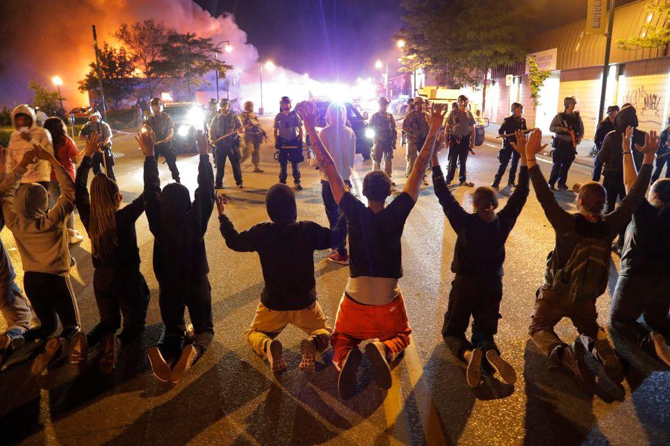 Demonstrators kneel before police inMinneapolis in the early hours of Saturday