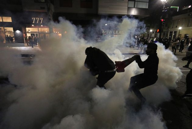 OAKLAND, CALIFORNIA - MAY 29: A demonstrator attempts to cover a tear gas canister that was deployed...
