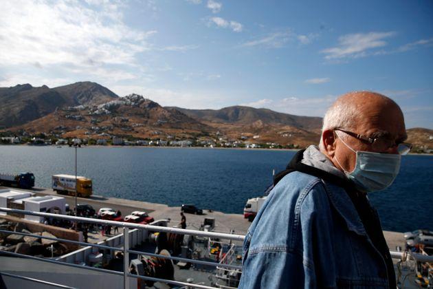 Επιβάτης σε καράβι με μάσκα, κοντά στο λιμάνι της Σερίφου.